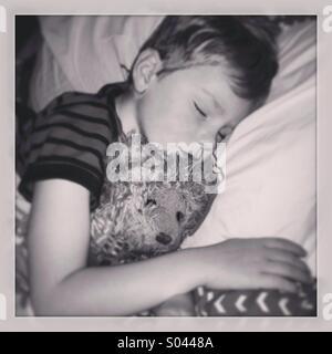 Garçon dormir avec nounours. Banque D'Images
