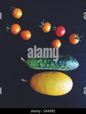 Tomates et concombres récoltés dans un jardin. Banque D'Images