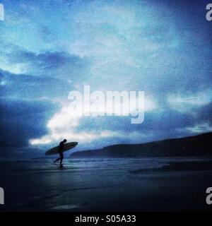 Un surfeur promenades sur la plage, d'un surf en fin de soirée à Watergate Bay. Newquay, Cornwall, Angleterre, Royaume Banque D'Images