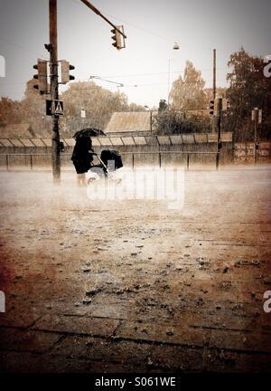 Une femme marche dans de fortes pluies avec un landau Banque D'Images