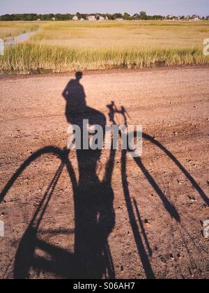 L'ombre d'un homme sur une bicyclette sur un chemin en Nouvelle Angleterre, USA. Banque D'Images