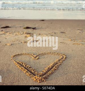 Forme de coeur dessiné dans le sable sur la plage Banque D'Images