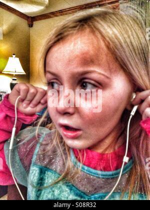 Une fille à l'écoute de la musique via des écouteurs. Banque D'Images