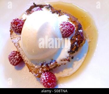 Pain doré avec glace à la vanille, sirop d'érable et les framboises. Banque D'Images