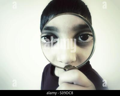 Little Boy holding magnifying glass Banque D'Images