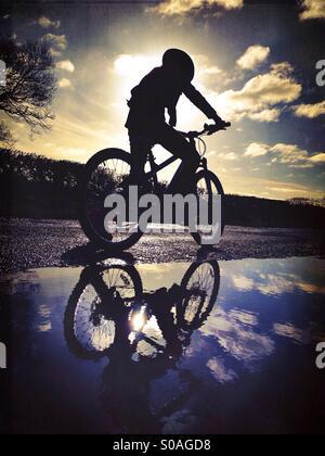 Jeune fille en vélo en silhouette reflétée dans la flaque Banque D'Images