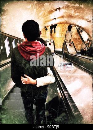 Couple sur le tube d'escaliers mécaniques, le centre de Londres, Angleterre, Royaume-Uni, Europe Banque D'Images