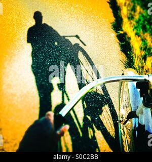 L'ombre d'un cycliste sur une piste cyclable. Banque D'Images