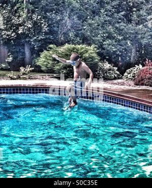 Garçon prend cannonball sauter dans une piscine Banque D'Images