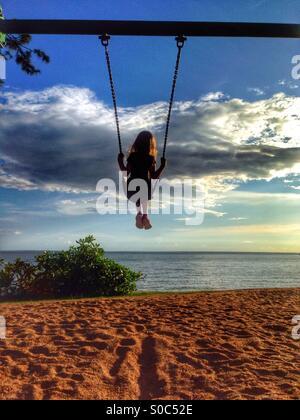 Jeune fille sur une balançoire à la plage. Banque D'Images
