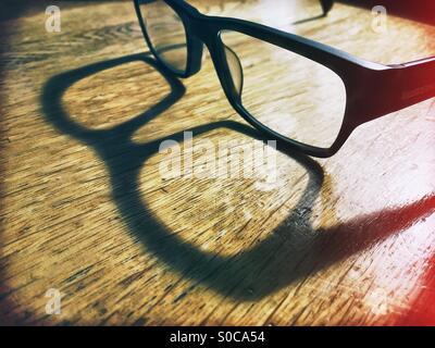 Une paire de lunettes de lecture d'un rebord épais assis sur un bureau en bois jette une ombre dans la lumière du soleil.