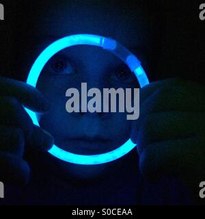 Boy looking through blue glow stick hoop Banque D'Images