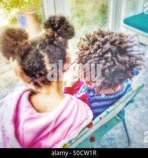 Deux enfants assis sur une chaise. Banque D'Images