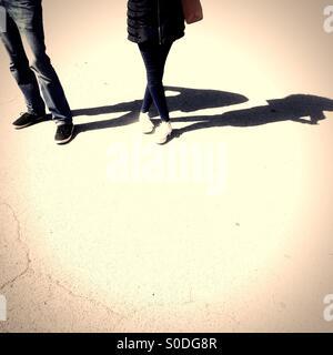 Couple debout sur le béton sur journée ensoleillée à l'ombre qui plane