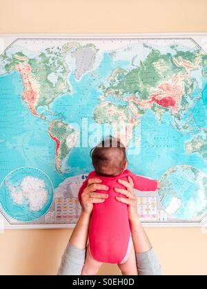 Hello World! Père tenant son bébé fille jusqu'en face de la carte du monde Banque D'Images