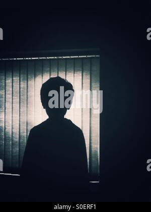 Silhouette d'un petit garçon par la fenêtre Banque D'Images