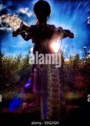 Jeune fille en vélo en silhouette Banque D'Images