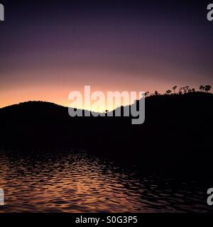 Purple haze le coucher du soleil, en raison de l'orange dans le lac. Les collines et les arbres sont noir profond, Banque D'Images