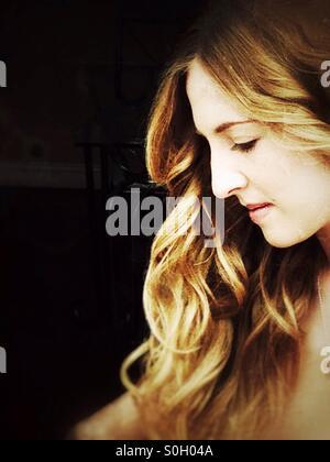 Young Caucasian woman with long blonde ondulés vu de profil. Banque D'Images