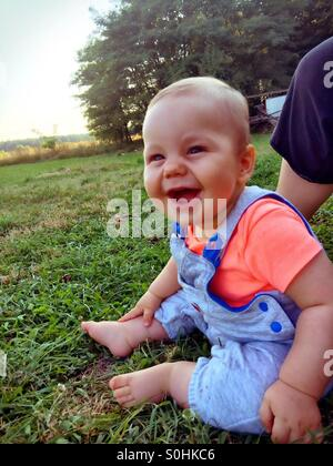 Smiling baby boy sitting on the grass Banque D'Images