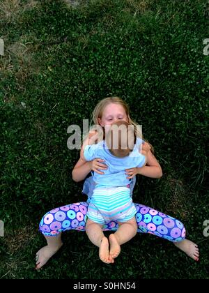 Fille couchée sur l'herbe à l'extérieur avec son frère Banque D'Images