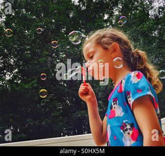 Little girl blowing bubbles Banque D'Images