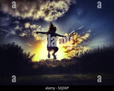 Jeune fille sautant par Sun en fin de soirée rétro-éclairé Banque D'Images