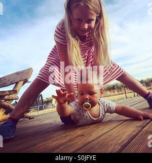 Une blonde vêtue d'une robe rayée rouge et blanc girl watching over et tenant son petit frère qui est d'apprendre Banque D'Images