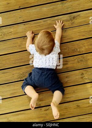 Vue depuis le sommet de 8 mois bébé garçon essayant de ramper sur une terrasse en bois , à l'extérieur à l'arrière Banque D'Images