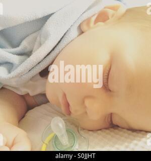 8 mois bébé garçon dormir paisiblement sur le lit des parents , couverts de lumière bleue couverture, avec une sucette Banque D'Images