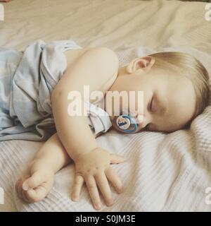 8 mois bébé garçon dormir paisiblement sur une chaude journée d'été sur le lit des parents recouvert d'une couverture Banque D'Images