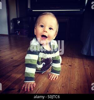 Happy Baby Boy apprendre à ramper sur un sol en bois, à l'intérieur dans le salon d'un appartement polonais Banque D'Images