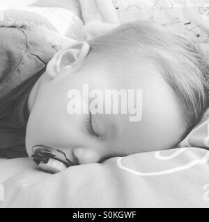 Un bébé de 9 mois garçon , ses dents, fiévreux est prendre une sieste avec sa sucette sur son lit des parents Banque D'Images