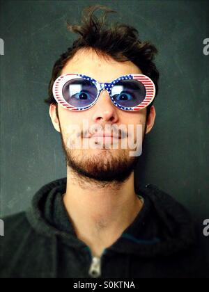 Un jeune homme portant des lunettes de drapeau américain. Banque D'Images