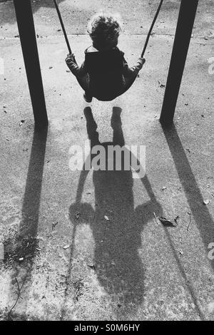 Garçon sur swing avec de longues ombres Banque D'Images