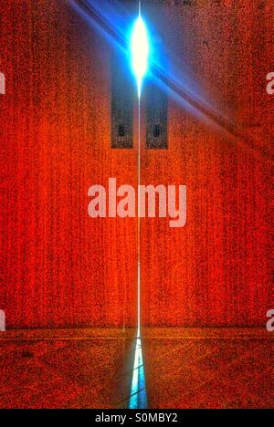 La porte rouge avec la lumière peeking through Banque D'Images