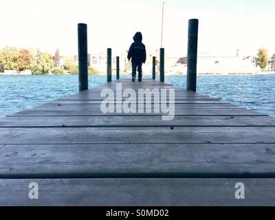 Jeune garçon debout sur une jetée Banque D'Images