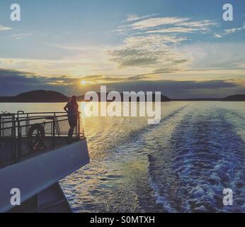 Femme debout à l'arrière du ferry pour le coucher du soleil. Banque D'Images