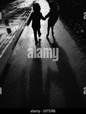 Silhouette de deux enfants se tenant la main Banque D'Images