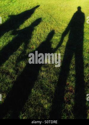 L'ombre d'une famille heureuse avec mains jointes tandis que dehors sur une balade hivernale dans un champ d'herbe Banque D'Images