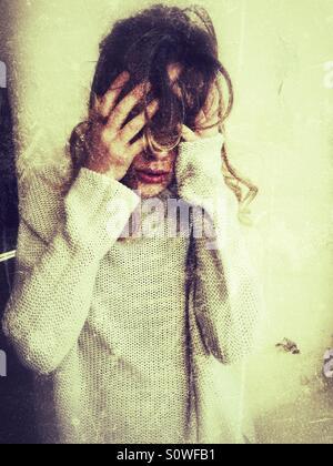 Jeune femme déprimée se cachant la tête dans les mains Banque D'Images