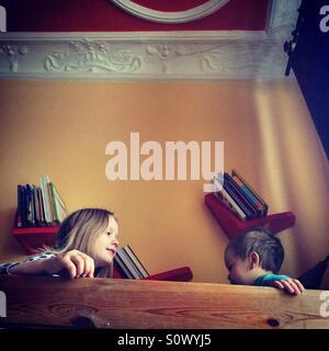 Frères et soeurs assis sur une couchette supérieure lit le matin Banque D'Images