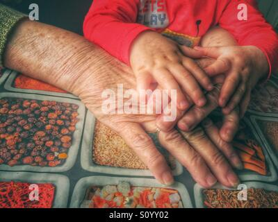 Grand-mère et bébé mains Banque D'Images