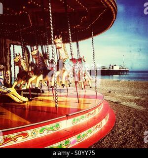 Carrousel à l'ancienne sur la plage de Brighton Pier avec en arrière-plan Banque D'Images