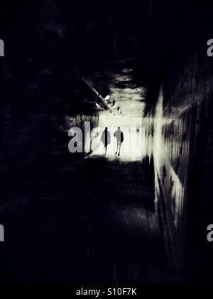 Deux figures émergent à partir d'un passage souterrain urbain dans la lumière. Banque D'Images