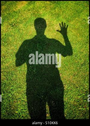 Ombre d'un homme avec un bras levé et tous les doigts et le pouce séparé dans un geste ondulant. C'est un beau jour Banque D'Images