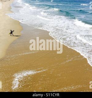 Un surfeur solitaire promenades sur la plage. Manhattan Beach, Californie, États-Unis. Banque D'Images