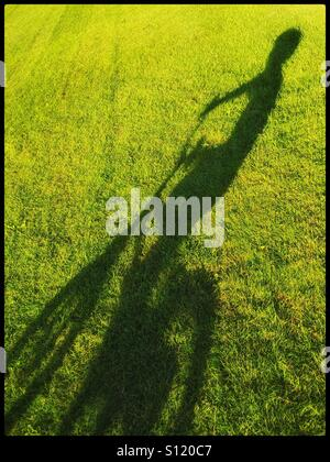 L'ombre d'un garçon de 6 ans sur son vélo dans une zone d'herbe. Une photo avec zone pour copier. Crédits photos Banque D'Images