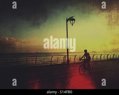Man riding son vélo par la mer au lever du soleil à Beyrouth Banque D'Images