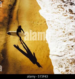 Un homme marche à la surf surfeur. Manhattan Beach, Californie, États-Unis. Banque D'Images